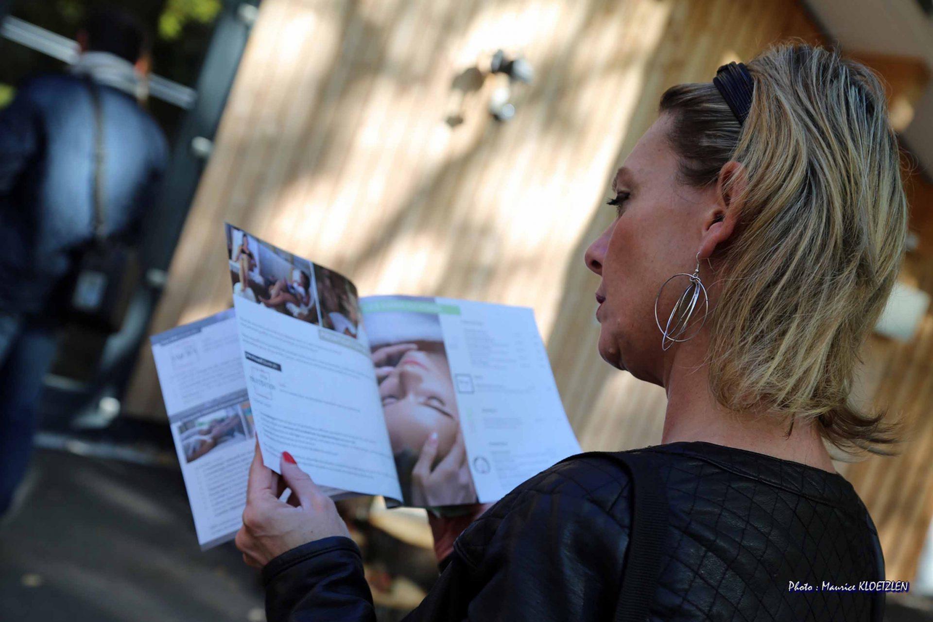 Personne qui consulte la brochure du spa nordique du Domaine du Hirtz